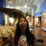Jasmine Duong smiling for the camera in a dinosaur museum