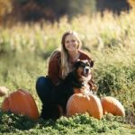 Young Woman in a pumpkin patch with a dog